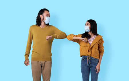 young asian friends greeting each other with their elbows. A new way of greeting to avoid the spread of coronavirus (COVID-19).