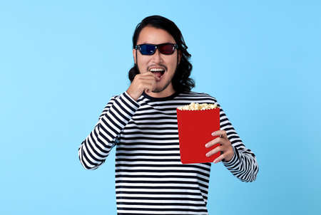 Happy Asian man wearing 3d glasses and eating popcorn while watching movie. Stockfoto