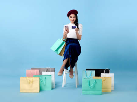 Beautiful Asian woman shopper sitting and carrying shopping bags with using credit card and mobile phone in hands on blue background.