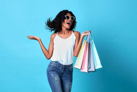 Portrait of an jovial beautiful woman holding shopping bags isolated on blue background.