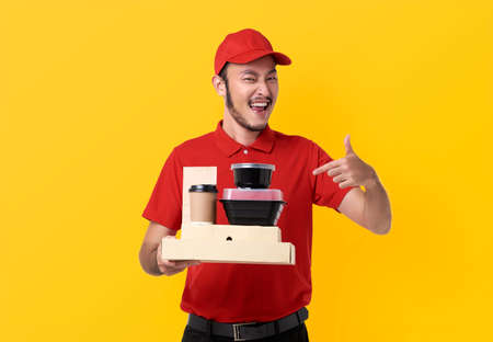 Asian delivery man wearing in red uniform holding lunch box and takeaway coffee isolated over yellow background