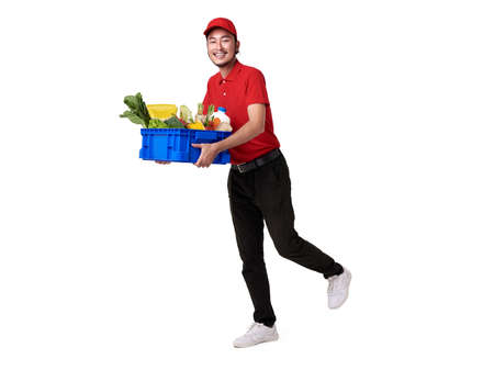 Asian delivery man wearing in red uniform holding fresh food basket isolated over white background. express delivery service.