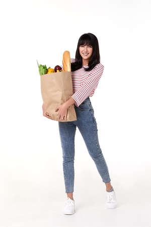 Happy Asian woman holding paper bag full of fresh vegetable groceries isolated on white background. Stockfoto - 154156300