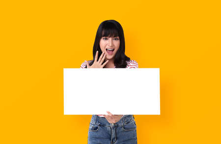 Excited young Asian woman with empty speech bubble studio shot on yellow background. Stockfoto