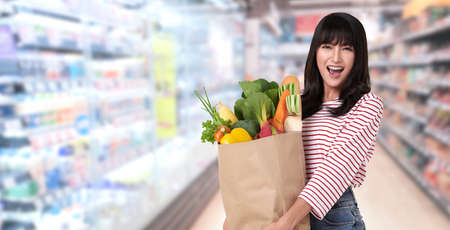 Happy Asian woman holding paper bag full of fresh vegetable groceries on supermarket background. Stockfoto - 153871595