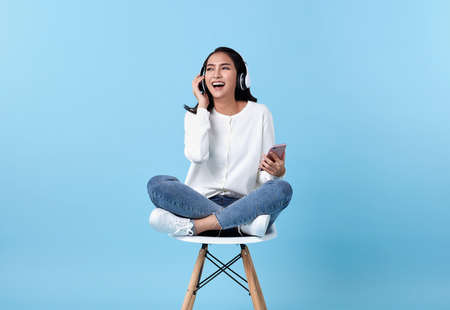 Young woman asian happy smiling wearing wireless headphones listening to music from smartphone on white chair isolate on bright blue background.