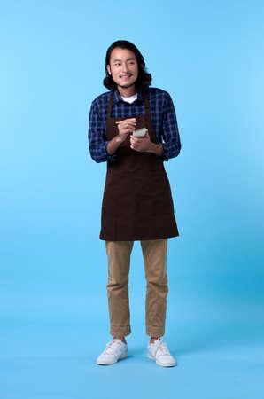 Portrait of service minded handsome asian man employee studio shot on blue background