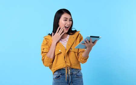 Excited young asian woman using tablet computer isolated on blue background Stockfoto - 154382533