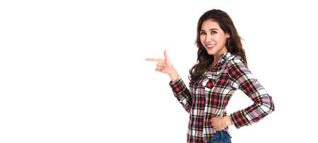 Happy young asian woman standing with her finger pointing isolated over white banner background with copy space. Stockfoto
