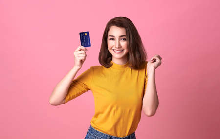 Young woman holding credit card  in casual yellow shrit with gorgeous in trust and confidence for money transaction isolated on bright pink background. Stockfoto - 154382536