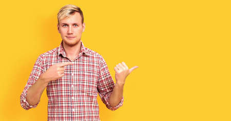 Happy young man standing with finger pointing isolated over yellow banner background with copy space. Stockfoto - 154382539