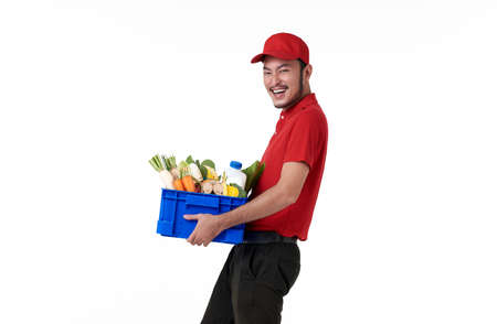 Asian delivery man wearing in red uniform holding fresh food basket isolated over white background.