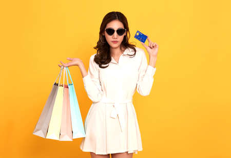 Portrait of an excited beautiful asian women wearing white dress and credit card holding shopping bags isolated on yellow background. Stockfoto