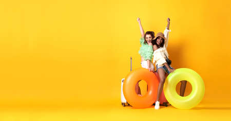 Cheerful friends woman dressed in summer clothes sitting on a suitcase and rubber ring on copy space yellow background.