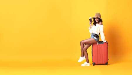 Cheerful young african woman dressed in summer clothes sitting on a suitcase on copy space yellow background.