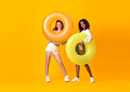 Cheerful friends woman dressed in summer clothes holding rubber ring over yellow background. Stockfoto - 155365171