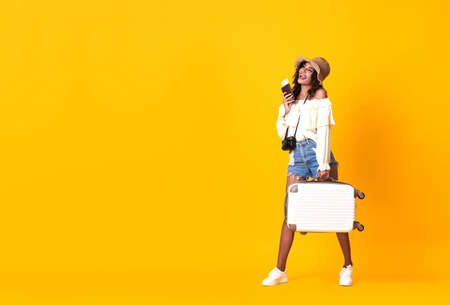 Cheerful african woman dressed in summer clothes holding passport with ticket while standing with a suitcase over yellow background. Stockfoto