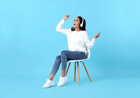 Happy Asian woman sitting on chair wearing wireless headphone listening to music from smartphone on blue background. Stockfoto
