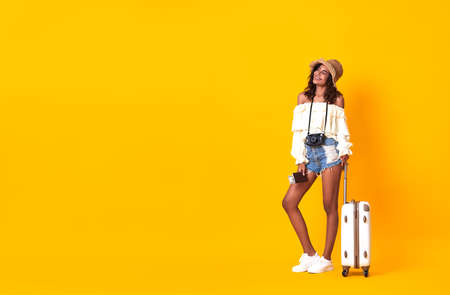 Cheerful african woman dressed in summer clothes holding passport with ticket while standing with a suitcase over yellow background. Stockfoto - 155365254