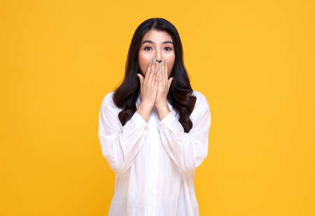 Surprised and Shocked asian woman covering mouth with hands isolated on bright yellow background.