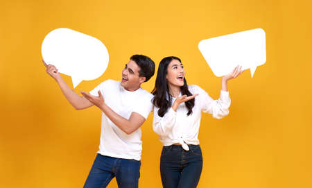 Smiling happy Asian couple holding blank speech bubbles on yellow background.
