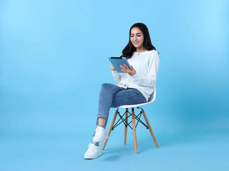 Young woman asian happy smiling in casual white cardigan with denim jeans.While her using tablet computer sitting on white chair isolate on bright blue background.