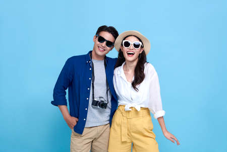 Happy playful Asian couple tourist dressed in summer clothes to travel on holidays isolated on blue background. Banco de Imagens