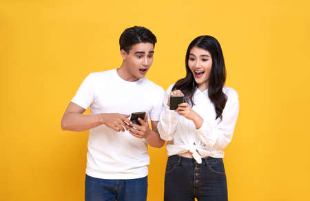 Amazed attractive young Asian couple looking message at smartphone together isolated on yellow background.