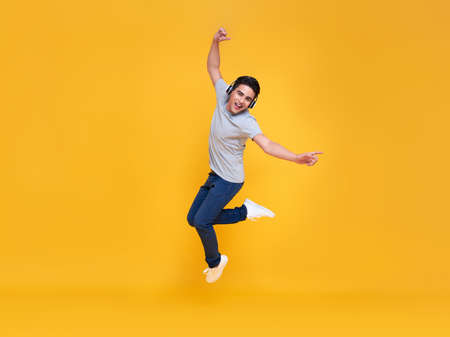 Young handsome Asian man smiling and jumping wearing wireless headphone listening to music isolated over yellow background.
