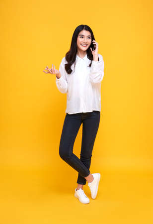 Smiling young casual Asian woman talking smart phone isolated over yellow background. Banco de Imagens