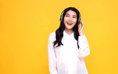 Happy smiling Asian woman wearing wireless headphones listening to music on yellow background.