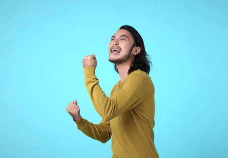 Cheerful young Asian man raising his fists with smiling delighted face, yes gesture, celebrating success on blue background.