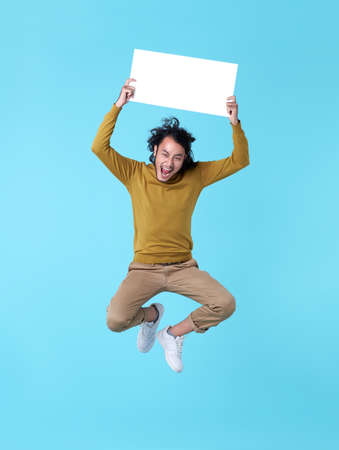 Happy energetic young Asian man jumping in mid-air holding blank speech bubbles on blue background.