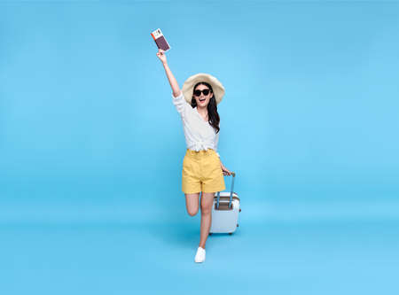 Happy young Asian tourist woman holding passport and boarding pass with baggage going to travel on holidays isolated on blue background. Banco de Imagens