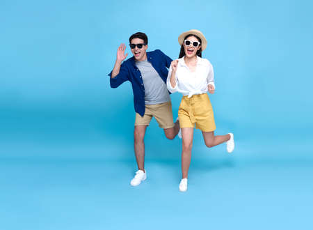 Happy energetic Asian couple tourist running to travel on holidays isolated on blue background.