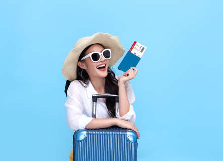 Happy young Asian tourist woman holding passport and boarding pass with baggage going to travel on holidays on blue background. Banco de Imagens