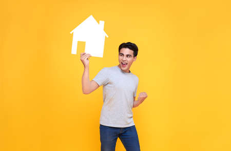 Handsome excited Asian man holding house cutout isolated on yellow background. Banco de Imagens
