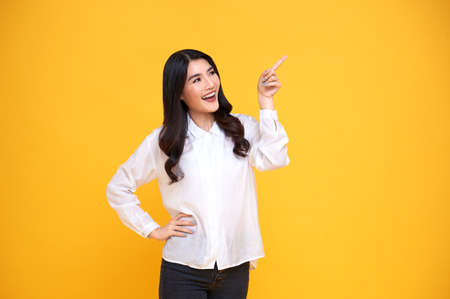 Happy young Asian woman standing with her finger pointing isolated over yellow banner background with copy space. Banco de Imagens
