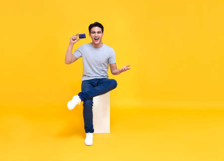 Happy handsome Asian man showing credit card in hand isolated on yellow background. Banco de Imagens