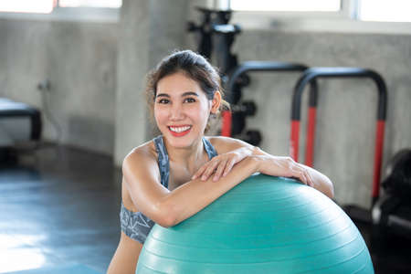 Asian woman at yoga gym posing leaning on her ball smiling and happy. Фото со стока