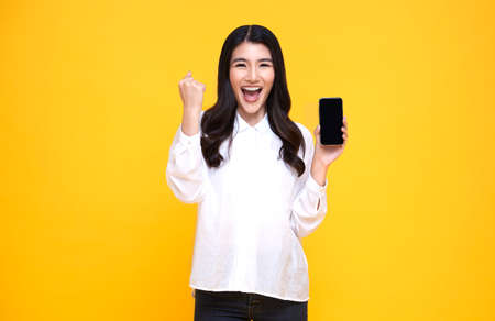 Happy young Asian woman showing at blank screen mobile phone and hand gesture success isolated over yellow background.