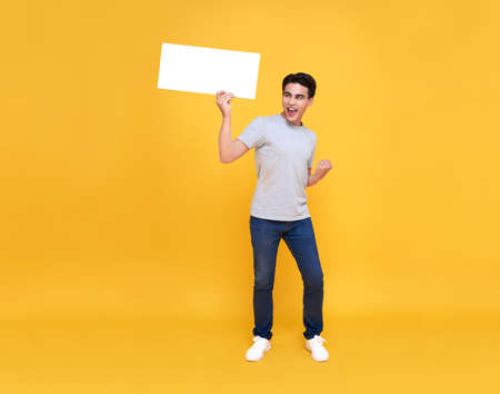 Smiling happy Asian man holding blank speech bubbles on yellow background.