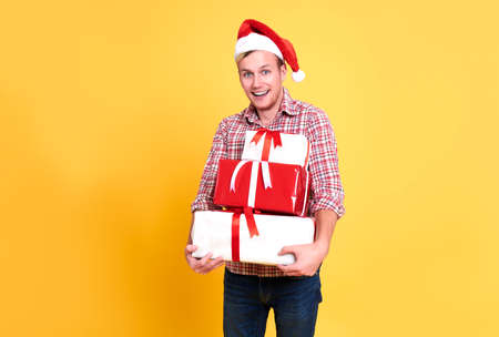 Handsome man wear santa hat holding a lot of gift box on yellow background.  christmas and happy new year concept.