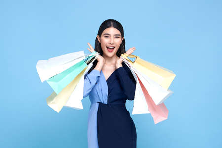 Happy beautiful Asian shopaholic women wearing blue dress and holding shopping bags isolated on blue background.