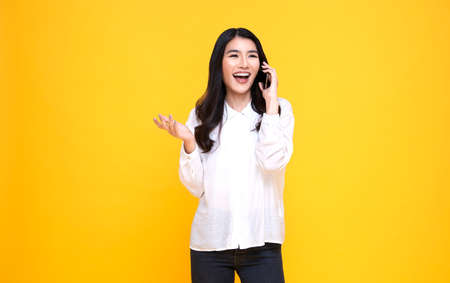 Smiling young casual Asian woman talking smart phone isolated over yellow background. Standard-Bild