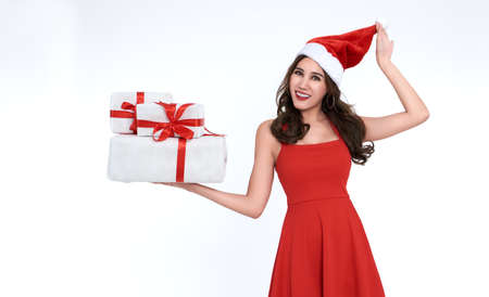 Cheerful young woman in red dress santa holding gift box for christmas isolated on white background.