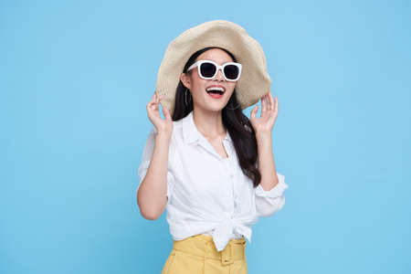 Happy Asian woman in summer casual clothes isolated on blue backgroud.