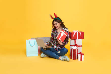 Asian woman using computer for shopping gift box online isolated on yellow background. cyber monday and christmas new year concept.