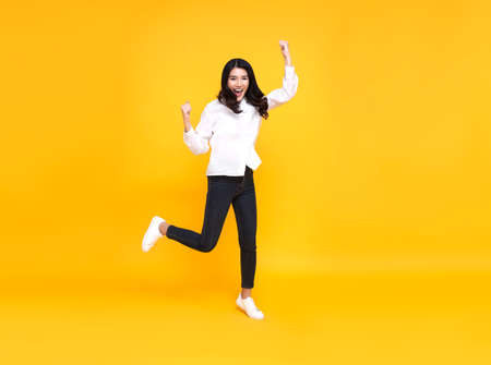 Happy Asian woman smiling and jumping while celebrating success isolated over yellow background.