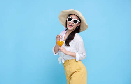 Happy Asian woman in summer casual clothes holding glass of fresh fruit juice drink isolated on blue backgroud. Banco de Imagens